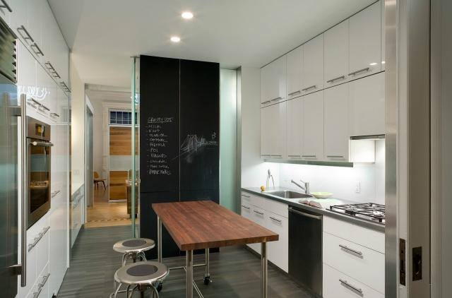 white kitchen with chalkboard and timber table