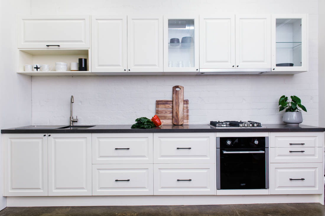 white kitchen with subway tiles and black benchtop