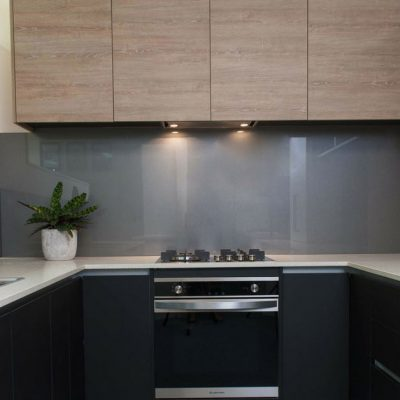 contemporary black kitchen with grey glass splashback