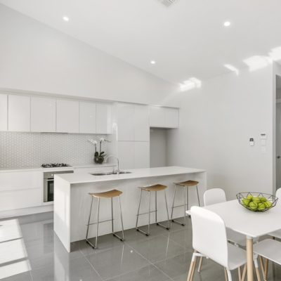 white handleless kitchen with white tile splashback