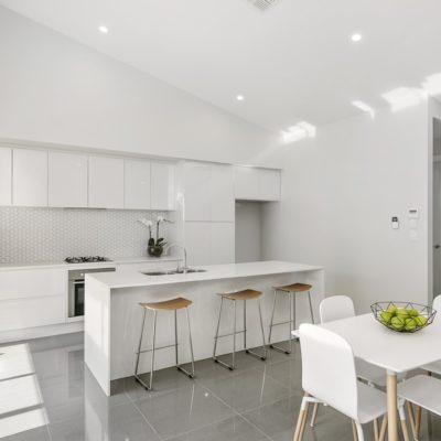 white handleless kitchen with white tile splashback