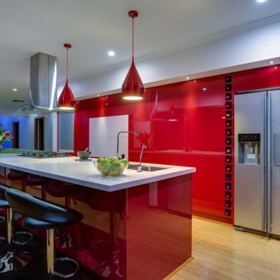 red gloss kitchen with double fridge and pendant lights