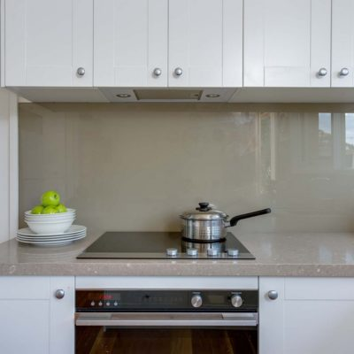 white kitchen with glass splashback, cooktop and oven