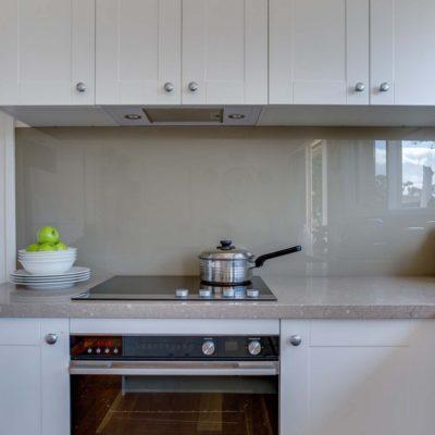 white kitchen with glass splashback