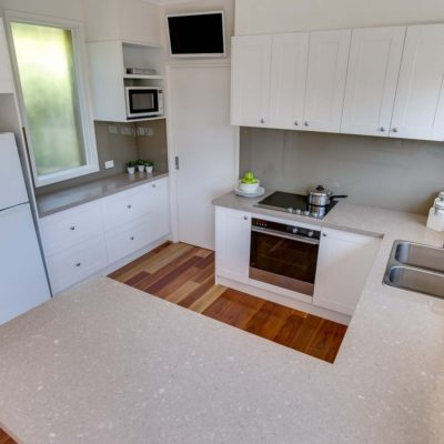 hamptons style kitchen with stone benchtop & glass splashback