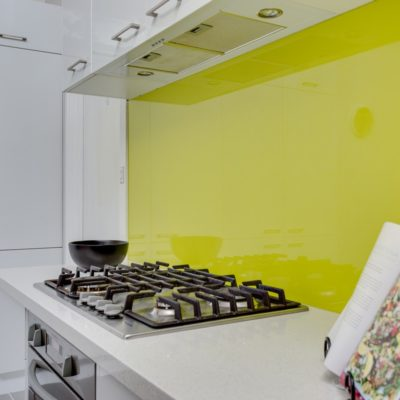 white kitchen with glass splashback and stove top and cookbook