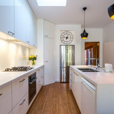 white kitchen with fridge, oven and dishwasher