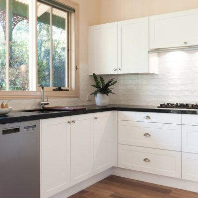 white hampton kitchen with black benchtop in kew