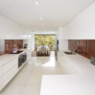 white handless kitchen with red glass splashback