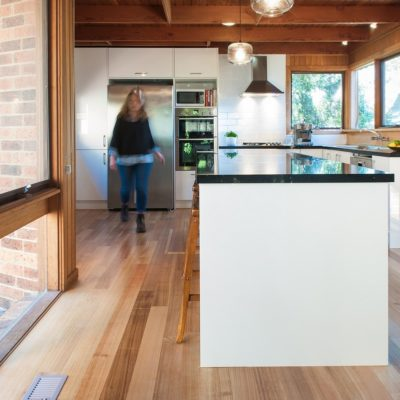 white kitchen with black benchtop and timber floors