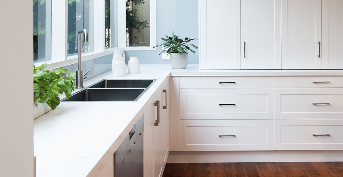 white shaker style kitchen with handles and pot plant