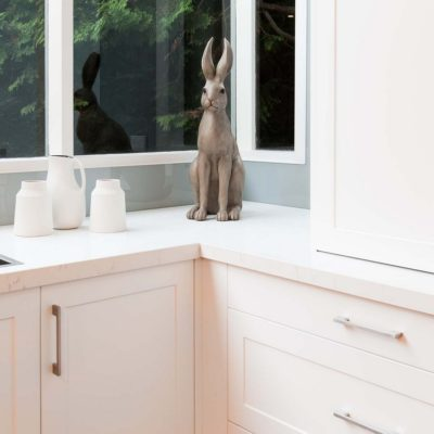 white kitchen with marble stone and rabbit statue