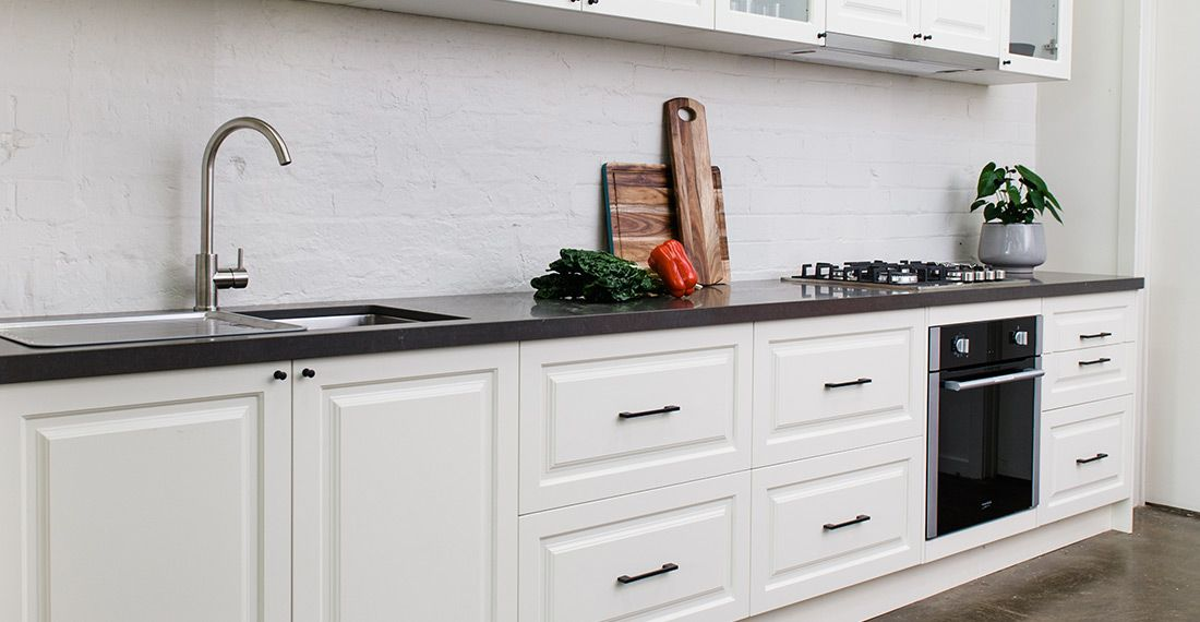 oven, kitchen sink, white kitchen drawers and black countertop with chopping boards and veggies