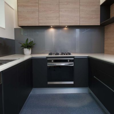 Zesta Kitchens Black Kitchen with white benchtop and timber overhead cupboards