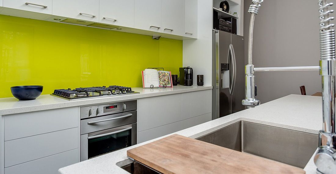 white kitchen with yellow glass splashback