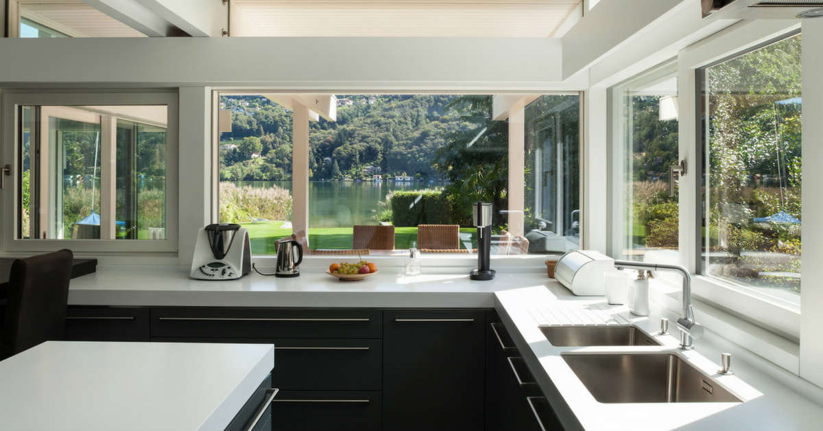 dark kitchen with white benchtop and beautiful view