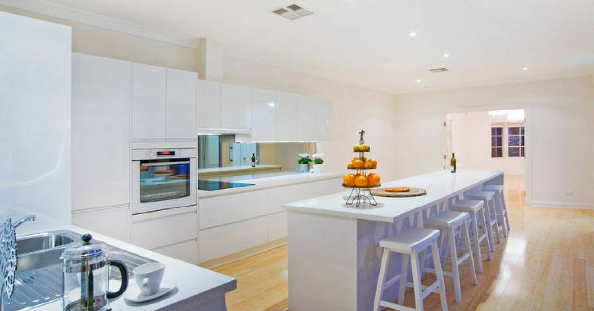 white kitchen with timber floors and fruit bowl