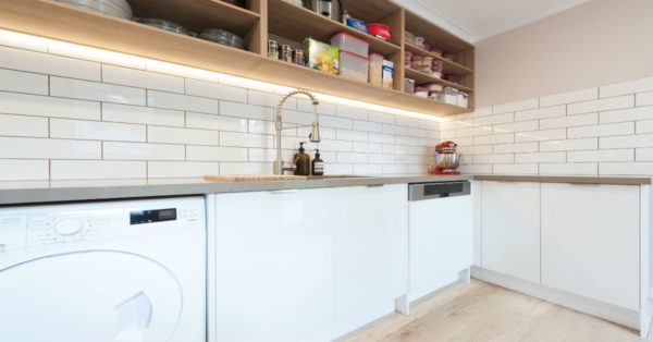 White laundry with subway tiles and wooden shelves