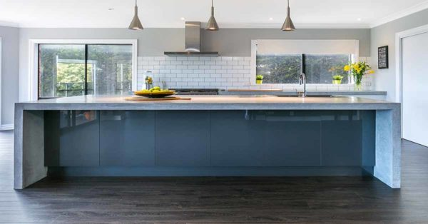 White Kitchen with concrete island and timber floors