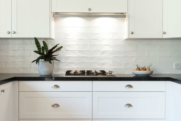 tiled splash back kitchen with white features and black bench top